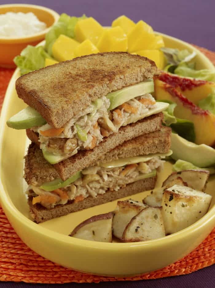Stacked avocado tuna salad sandwiches plated with salad