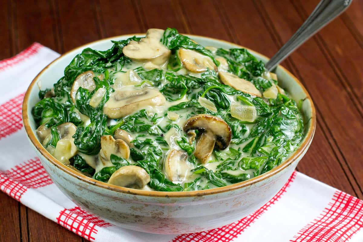 Bowl of creamed spinach with mushrooms on red and white napkin placed on wooden table.
