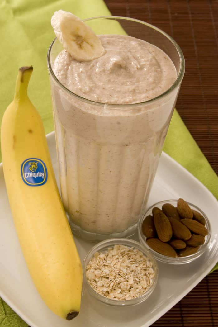 Smoothie in glass with banana slice for decoration, plated with banana and small bowls of almonds and oatmeal.