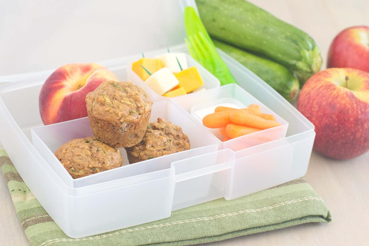 Bento box filled with mini muffins, a peach, cheese cubes, carrots and ranch on green napkin. Zucchini and apples in background