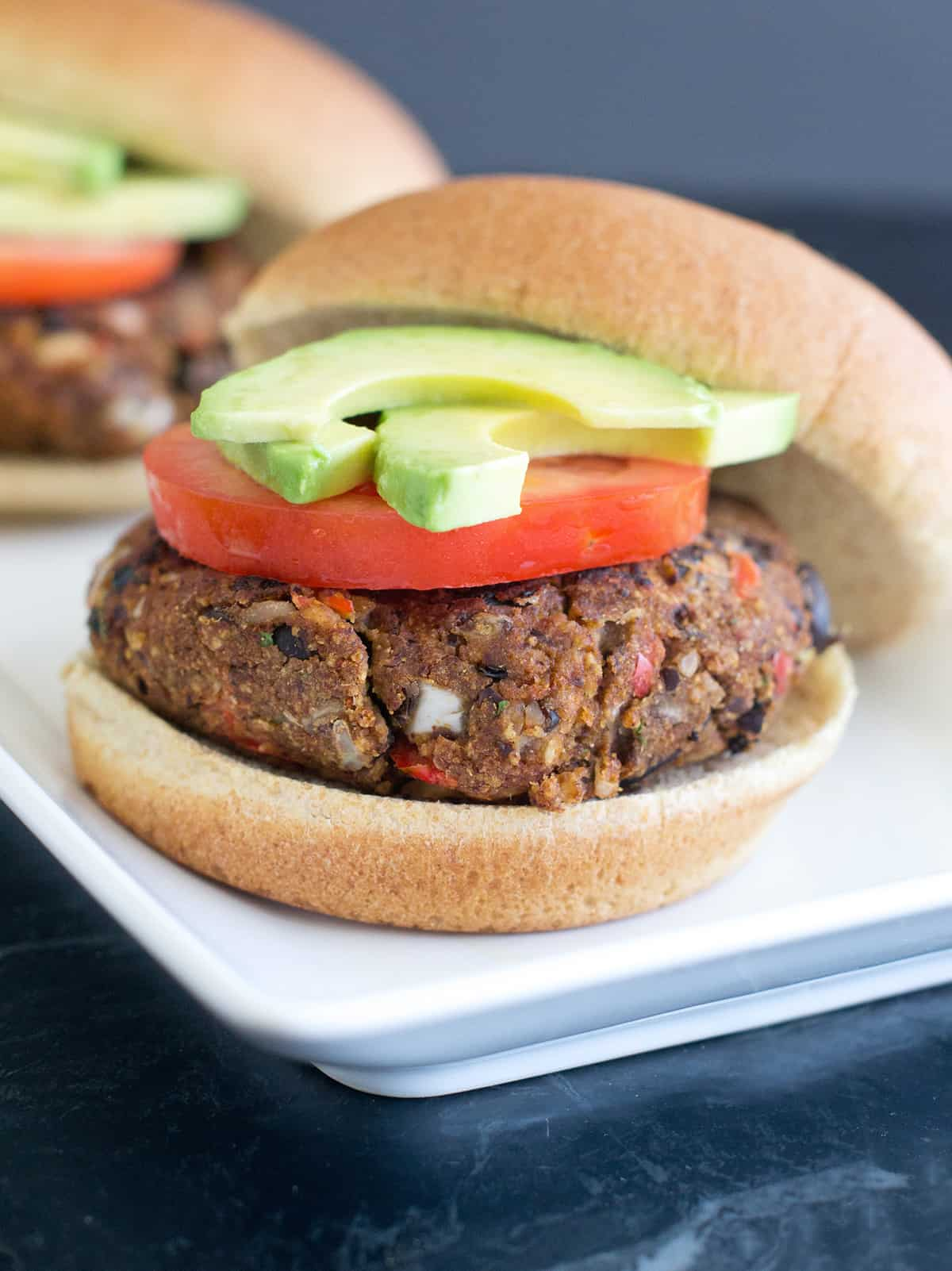 Close up of black bean burger topped with tomato and avocado slices and plated on rectangle white plate