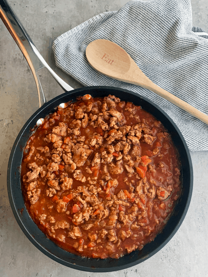 Skillet full of sloppy joes filling with wooden spoon and towel in background.