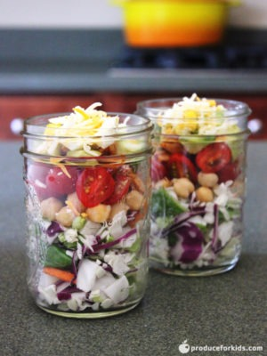 Easy School lunch ideas: BBQ Chicken Chopped Salad being shown in two glass mason jars on top of a countertop.