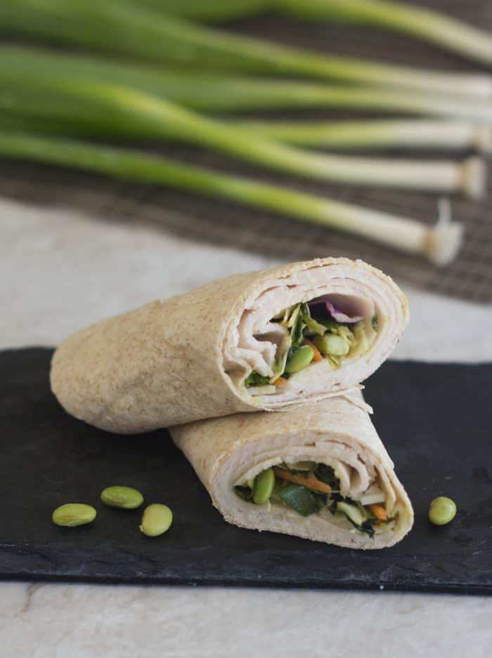 Close up of wrap on slate slab with green onions in background