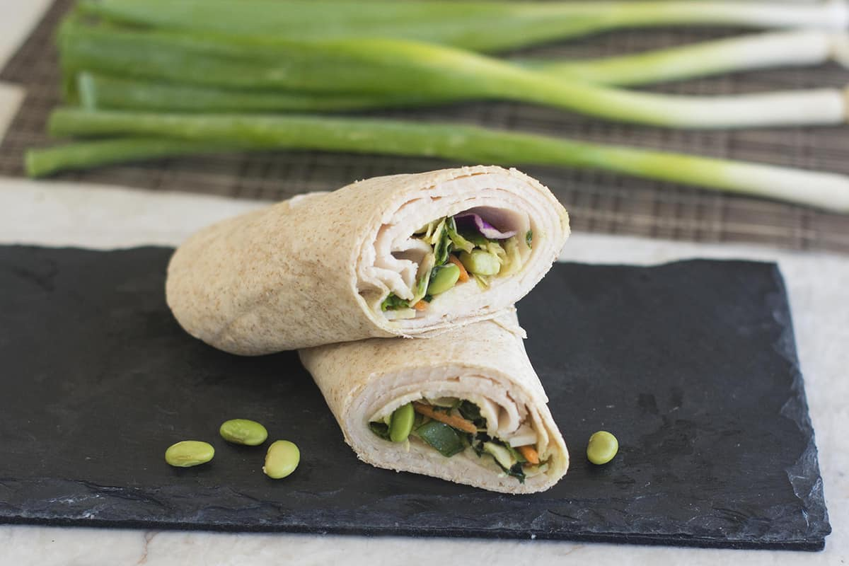 Wrap on slate slab with green onions in background
