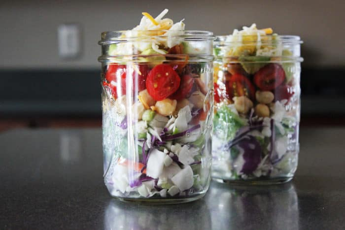 Two mason jars salad on counter