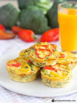 Easy School lunch ideas: Broccoli and Cheese Quiches being shown on a white plate with a large glass of orange juice behind the plate all on top of a countertop.