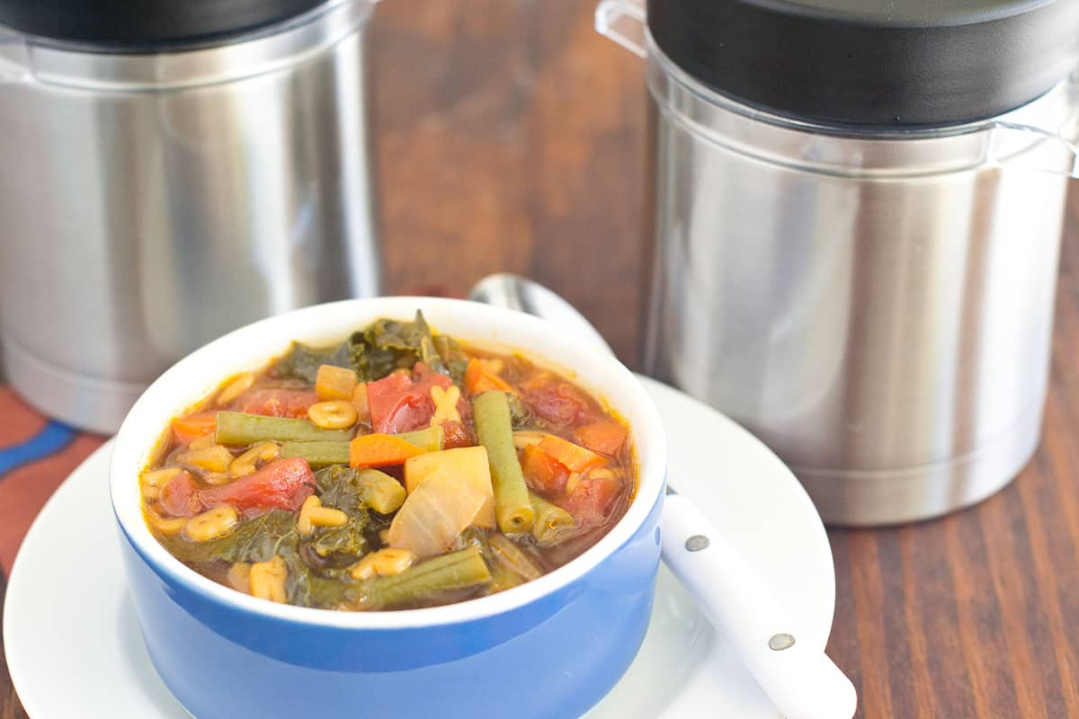 Vegetable soup in blue bowl on white plate with spoon. Two thermos containers shown in background