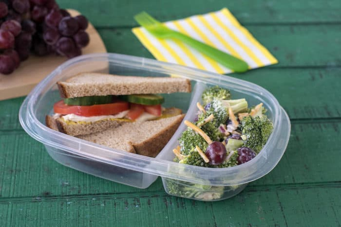 Bento box containing sandwich and broccoli grape salad on green wood background. Grapes on cutting board and a green plastic fork resting on a yellow and white striped napkin in background.