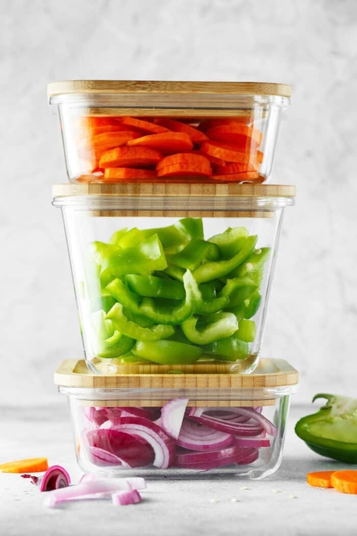 Chopped vegetables in stacked glass containers.