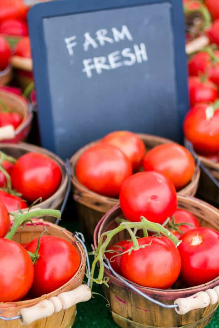 Farm fresh tomatoes in baskets at farmers market.