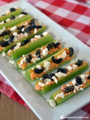 Greek Stuffed Celery - This easy celery recipe is stuffed with hummus and topped with crumbled feta cheese and chopped olives. Add a little more flair with chopped tomatoes, peppers or cucumbers. So easy, even kids can make these themselves!