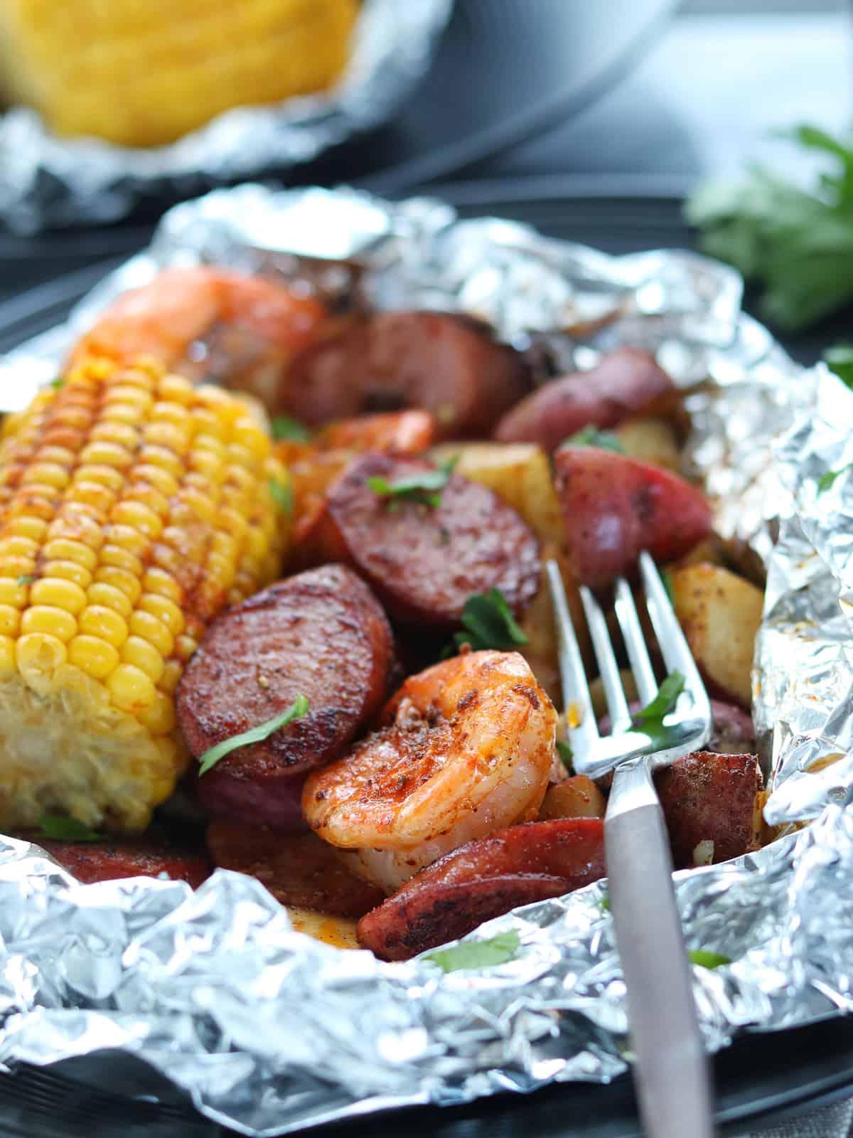 Close up shot of shrimp boil foil packets with fork