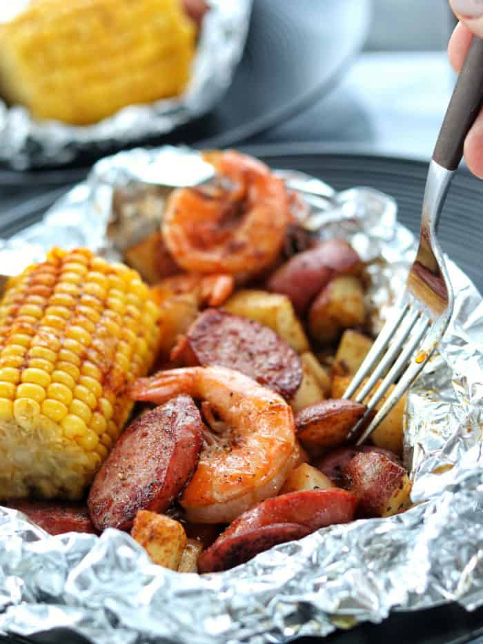 Foil packet opened up with shrimp boil meal inside, including shrimp, sausage, potatoes and corn on the cob. Fork digging in to eat.