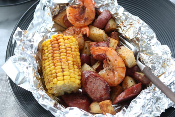 Top down view of foil packet opened up with shrimp boil meal inside, including shrimp, sausage, potatoes and corn on the cob.