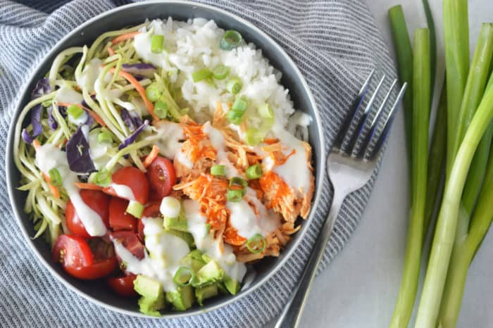 Buffalo chicken rice bowl on striped napkin