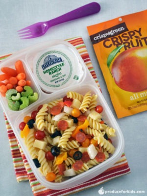 Easy School lunch ideas: Pizza Pasta Salad bento box being shown with a purple fork and dried fruit surrounding the box all on top of a white countertop.