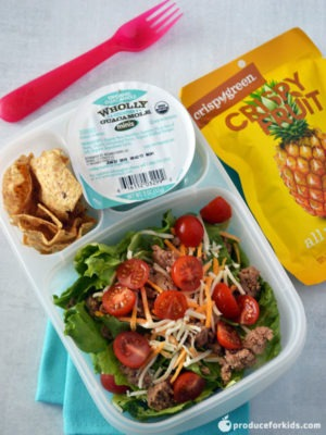 Easy School lunch ideas: Taco salad bento box being shown with a red plastic fork and dried fruit surrounding the box all on top of white countertop.