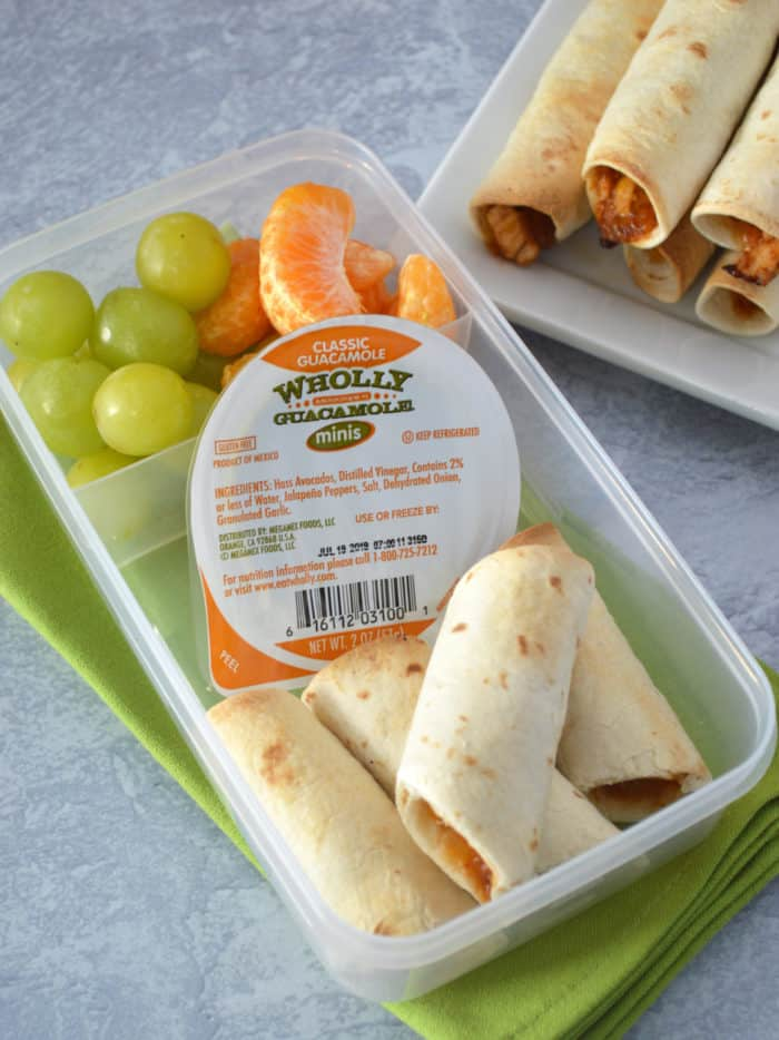 Bento box with taquitos, package of guacamole, green grapes and mandarin segments on green napkin with plate of taquitos in background