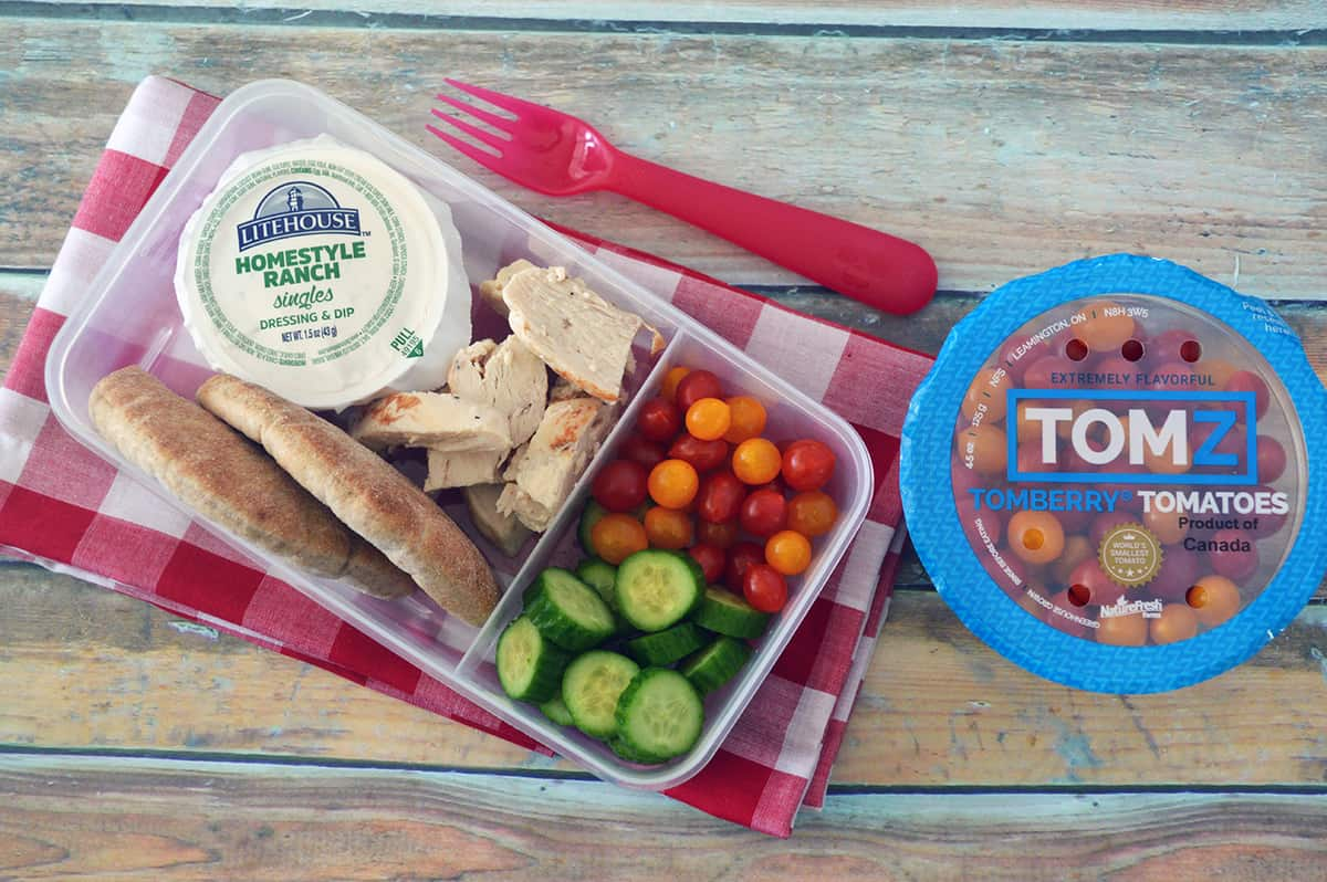 Bento box filled with chicken, pita bread, small tomatoes, cucumber slices and Ranch dip, placed on red checkered napkin.