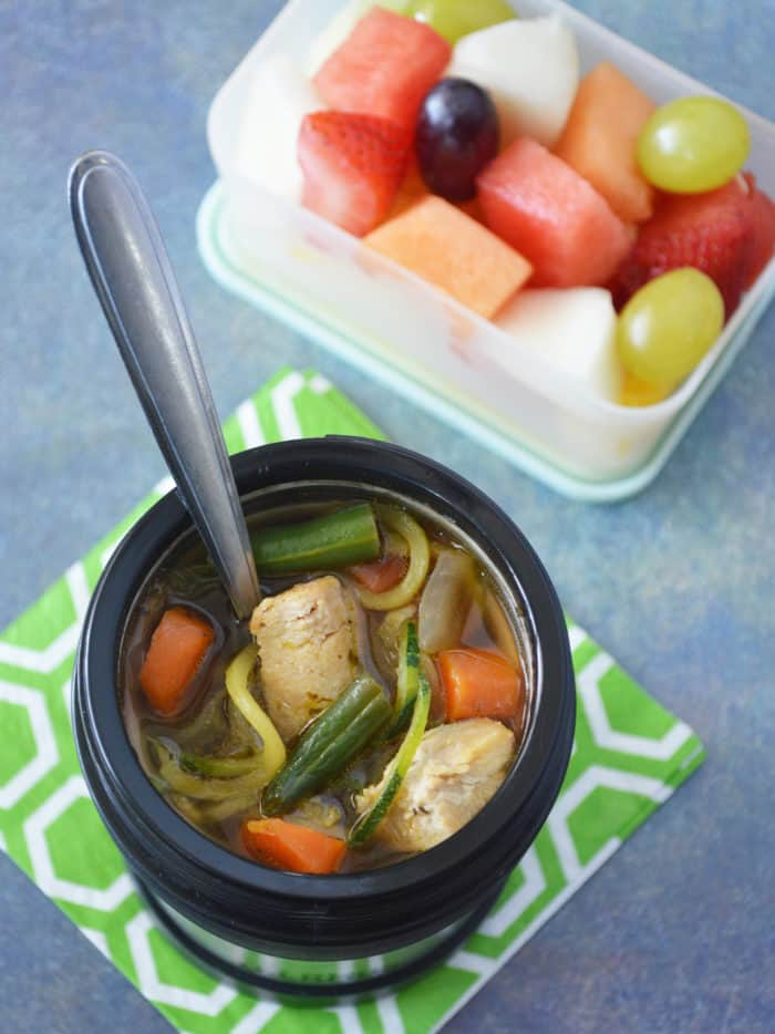 Thermos on green napkin filled with chicken zoodle soup. Container of fruit salad next to it.