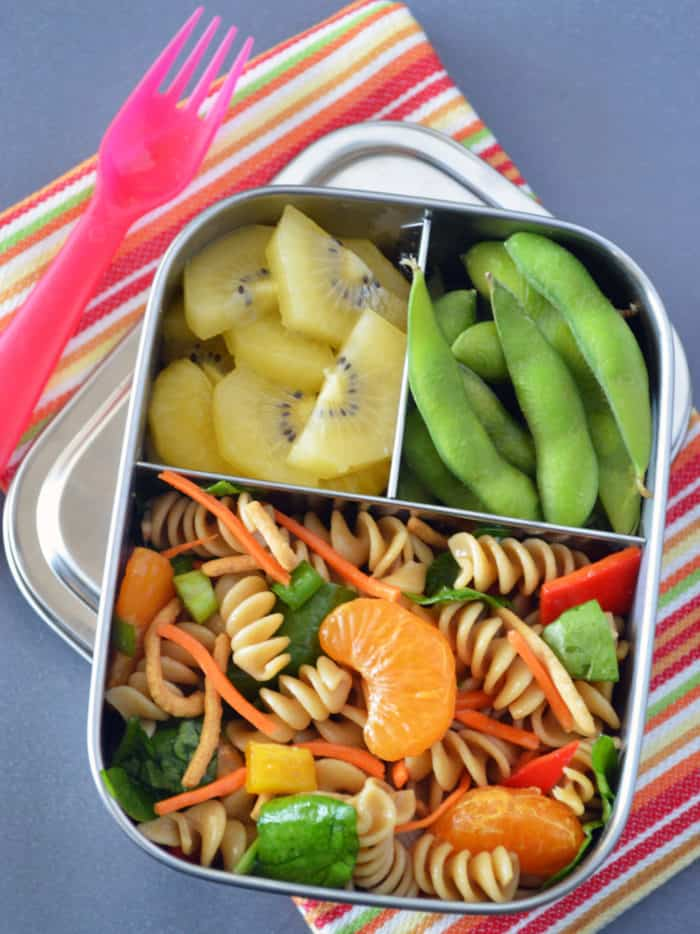 Metal bento box filled with pasta salad, kiwi and edamame on striped napkin and a pink plastic fork