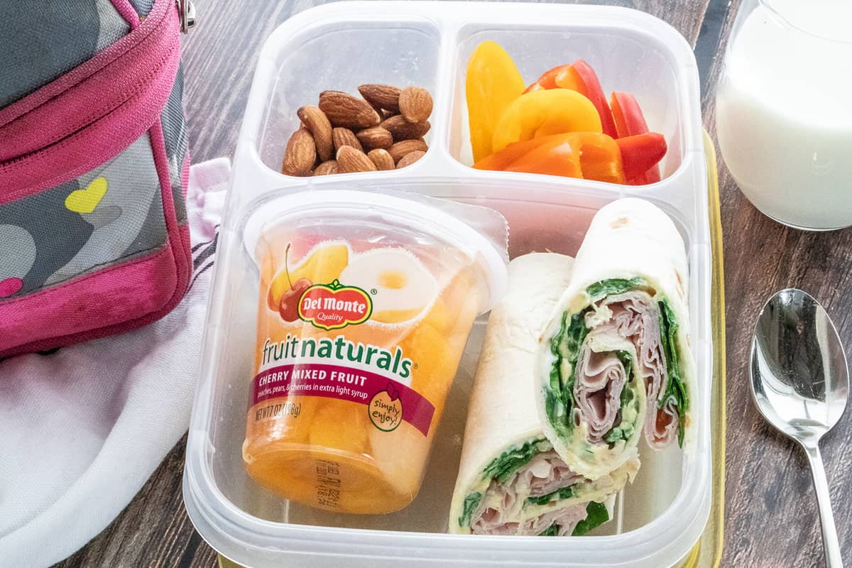 Ham & Spinach Wraps in Lunchbox with fruit cup, alomonds, and peppers