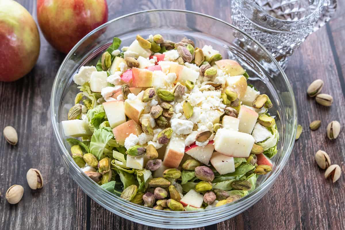Bowl of shredded Brussels sprouts salad topped with chopped apples, pistachios and feta cheese on wood background. Scattered pistachios and apples in background