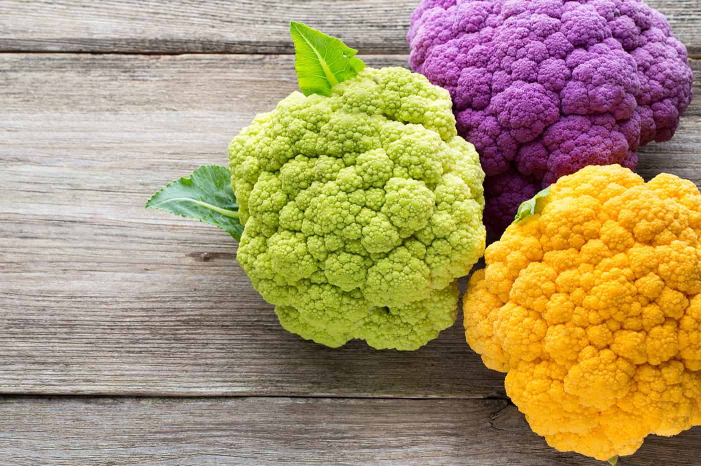 Rainbow of organic cauliflower on the wooden table.