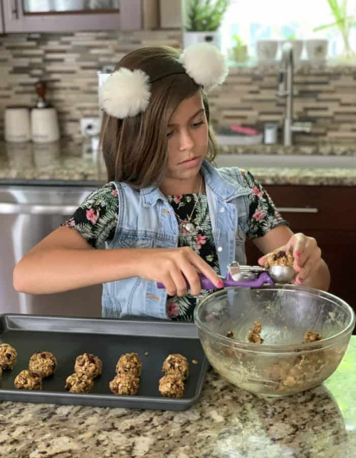 Girl scooping energy bite mixture using cookies scoop. Tray of already prepped energy bites in front of her.