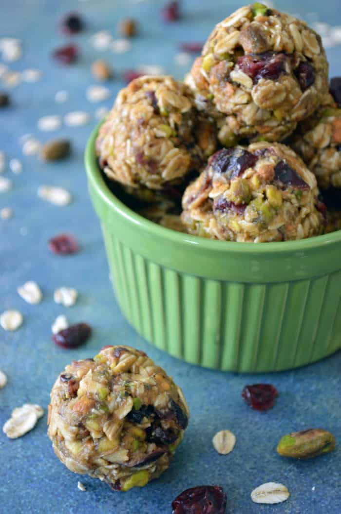 Bowl of energy bites with scattered dried cranberries, pistachios and oats in background. These cranberry and pistachio no-bake energy bites will help fill kids up and keep hunger at bay until dinner.