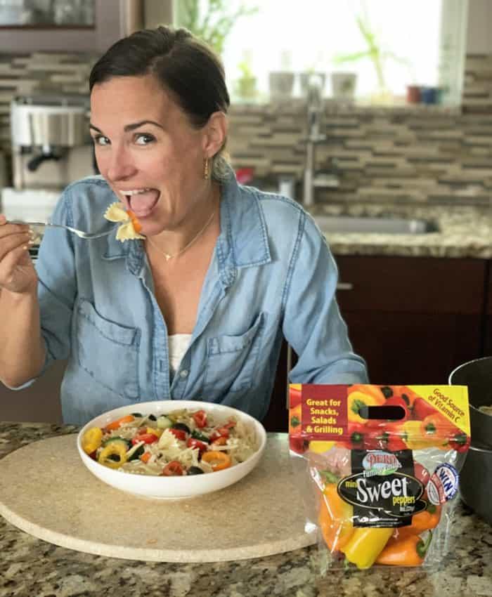 Woman taking bite of pasta salad