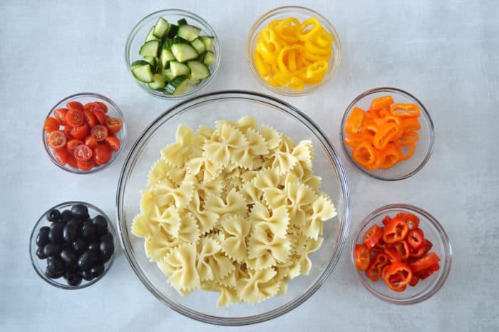 A large bowl of cooked bowtie pasta surrounded by smaller bowls of chopped black olives, tomatoes, cucumber, and yellow, orange and red mini sweet peppers.