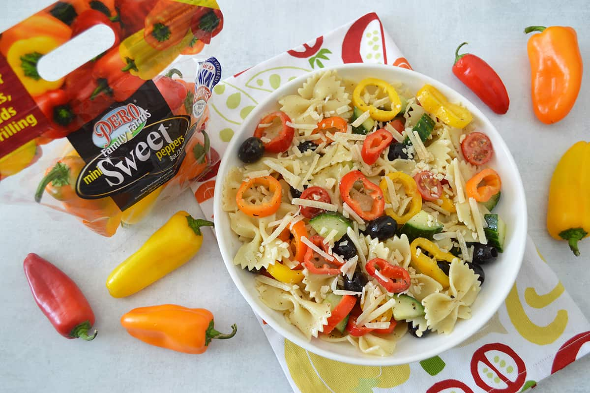 Rainbow Italian Pasta Salad in white bowl placed on top of colorful dish towel. Bag of Pero mini sweet peppers in background with a few scattered mini sweet peppers around the bowl.
