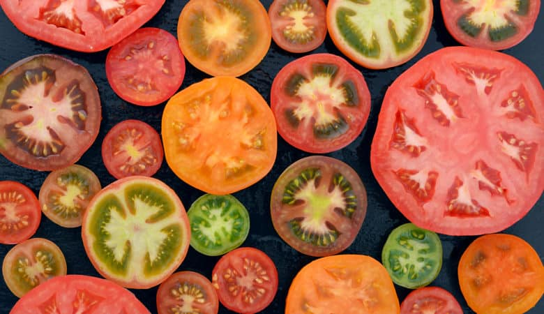 Different varieties of tomatoes sliced on black background