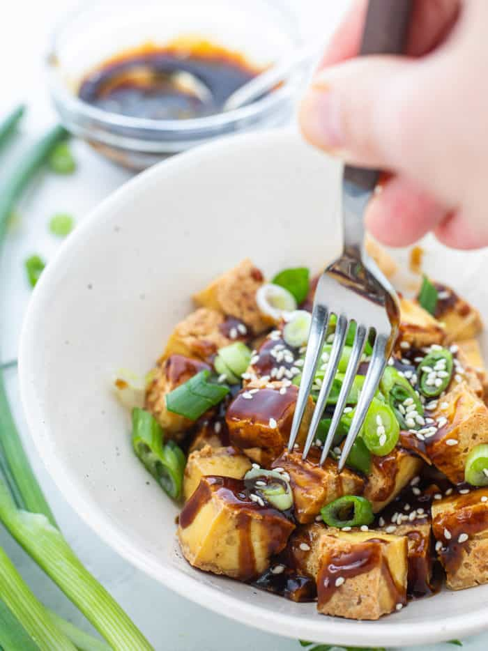 Fork digging into a white bowl with crispy tofu drizzled with sauce and sprinkled with green onions and sesame seeds