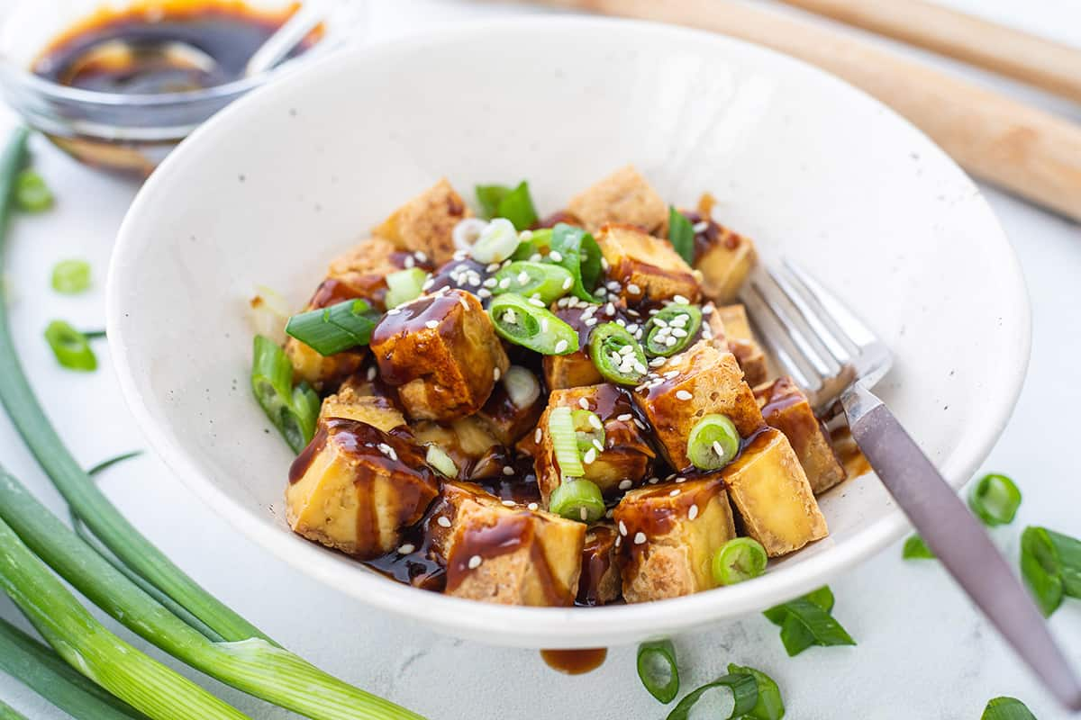 White bowl with crispy tofu drizzled with sauce and sprinkled with green onions and sesame seeds, plated with a fork.