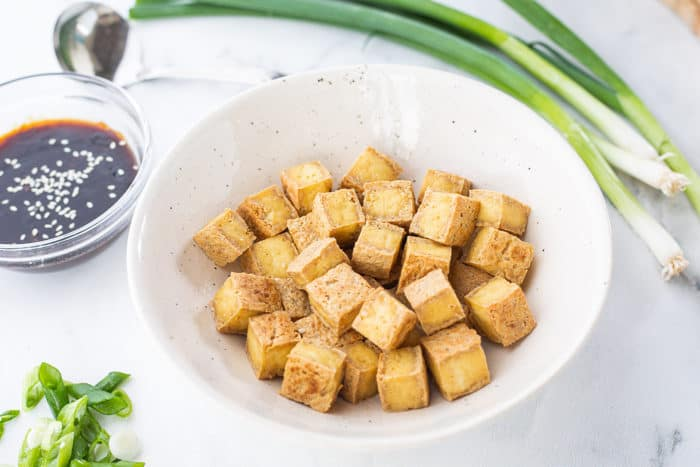 Crispy baked tofu in white bowl with whole green onions and a small bowl of sauce in background