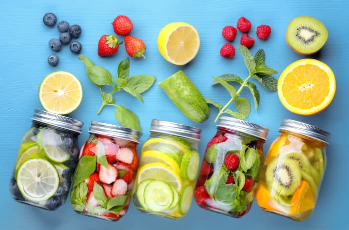 masos jars filled with water and various fruits on blue background
