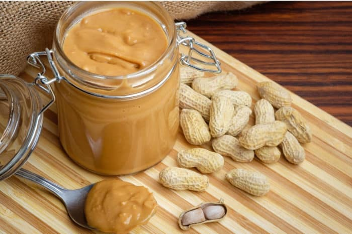 Peanut butter in jar on cutting board with peanut scattered