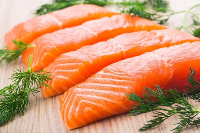 4 salmon filets lined up with fresh herbs