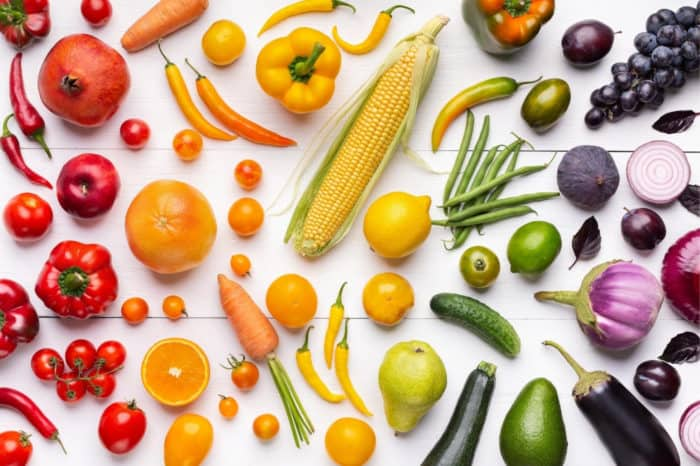 Various fruit and vegetables on white wood background