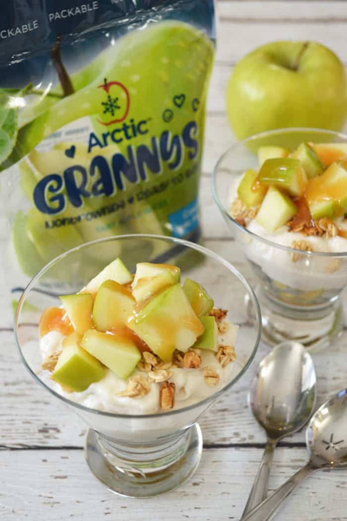 Close up of apple parfait with bag of apple slices and two spoons on white wooden background