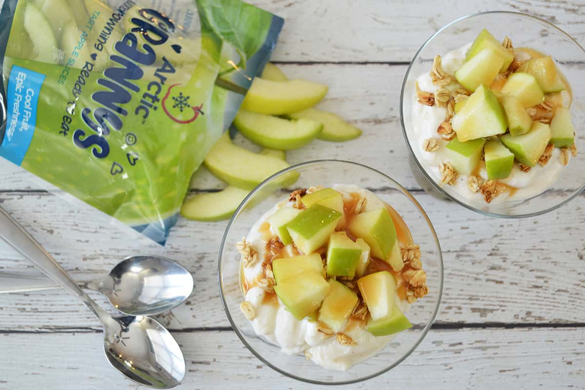 Overhead shot of two apple parfaits with open bag of apple slices and two spoons on white wooden background