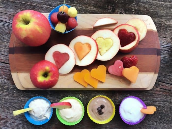 Fruit and cheese cut into shapes on cutting board with assorted dips