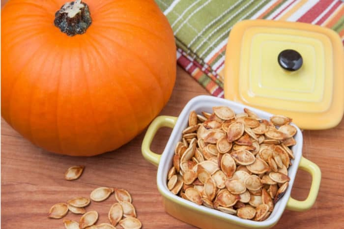 roasted pumpkin seeds in small bowl with pumpkin in background