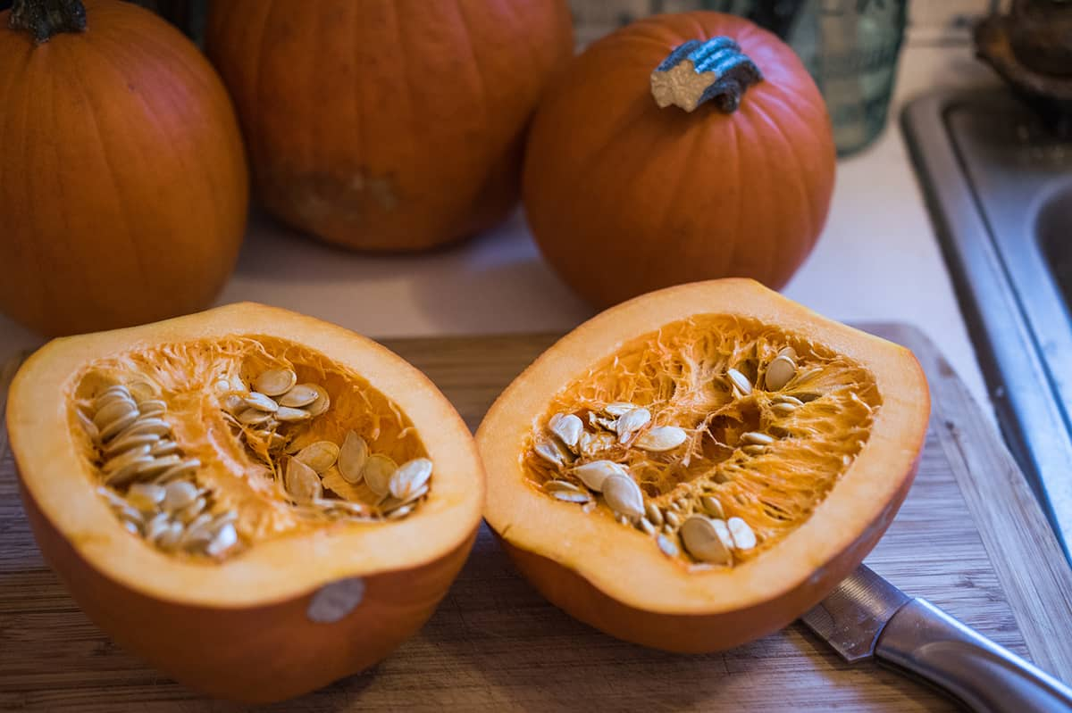 Cut sugar pumpkin on cutting board for Healthy Pumpkin Recipes