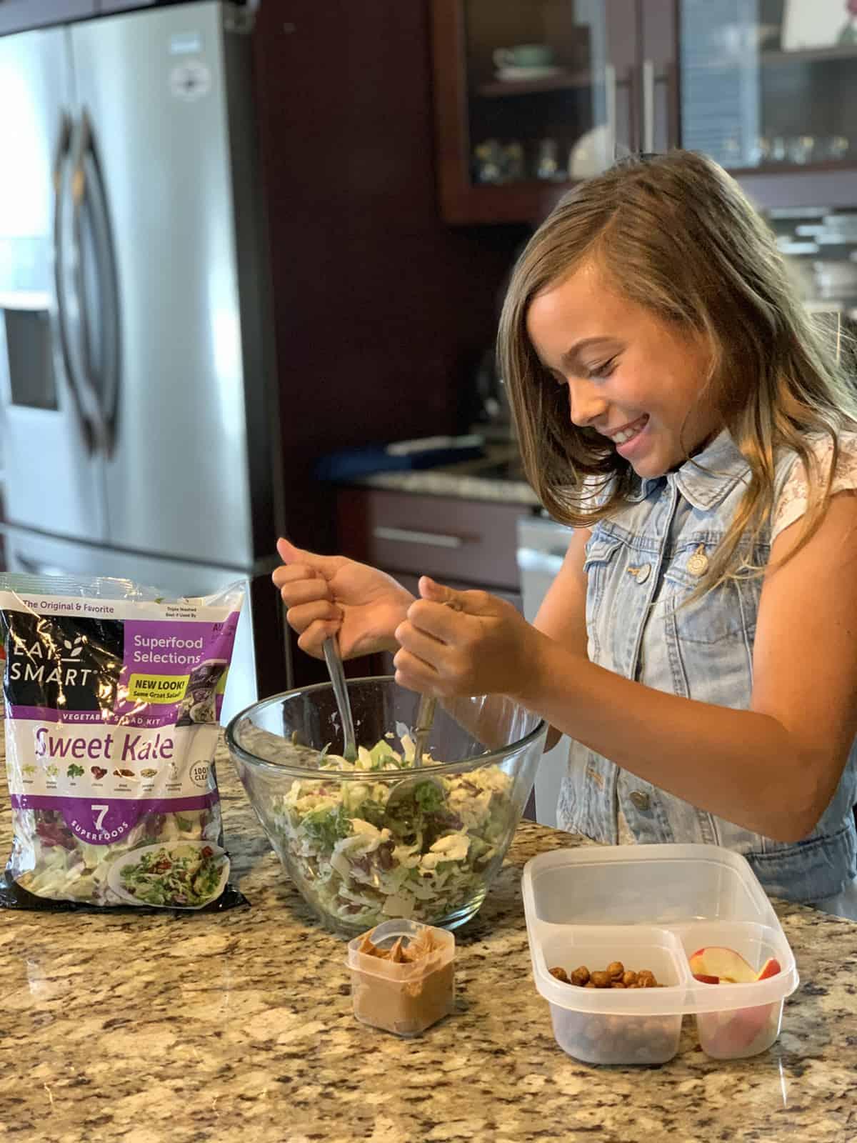 Girl tossing sweet kale salad salad in bowl