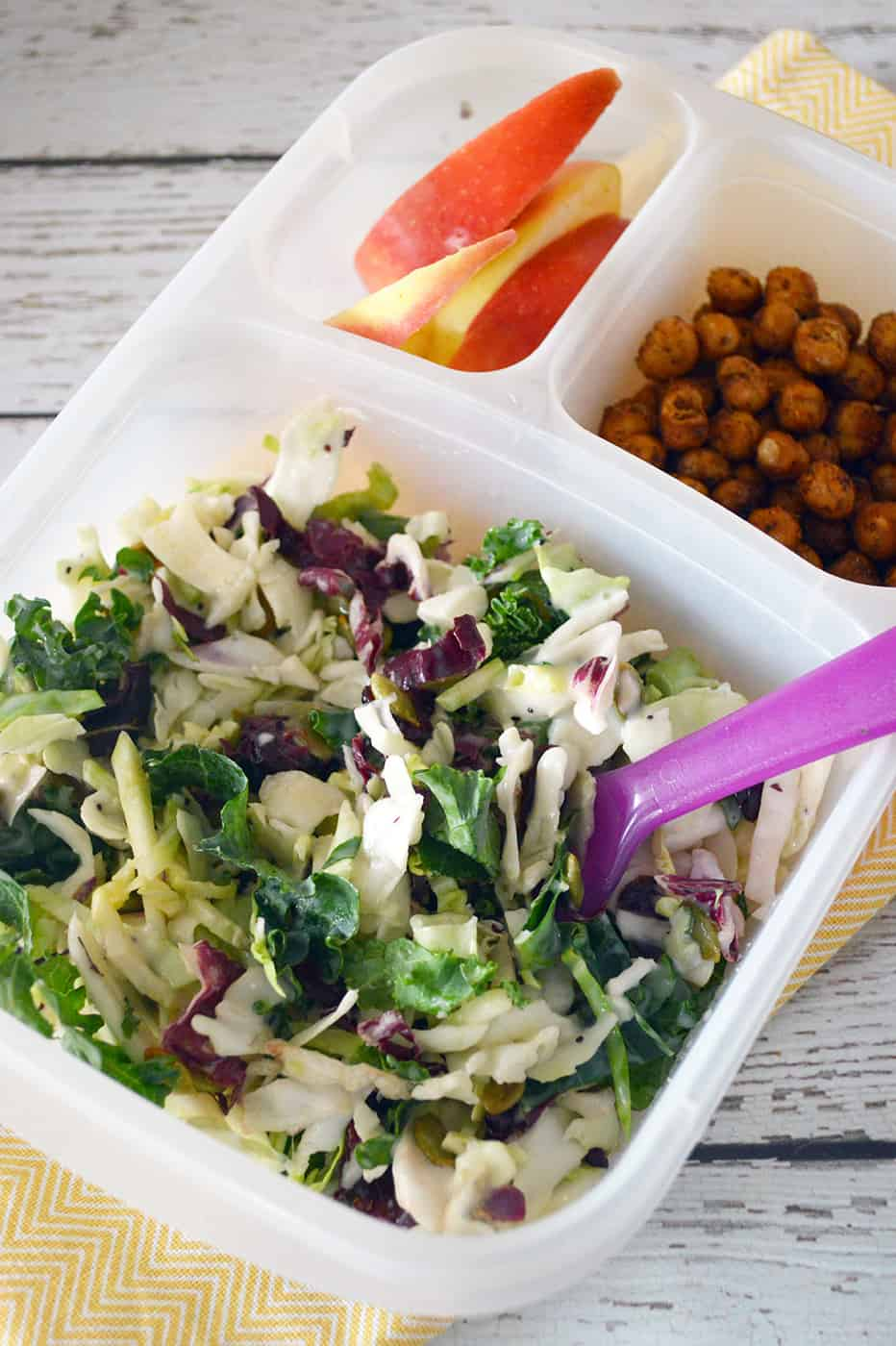 Bento box with sweet kale salad, apples and roasted chickpeas