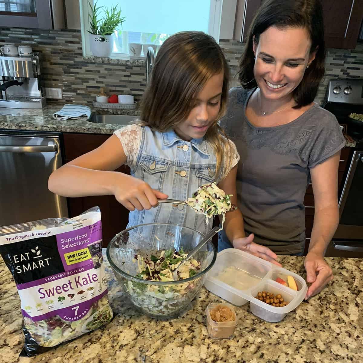 Girl and mom assembling sweet kale salad bento box